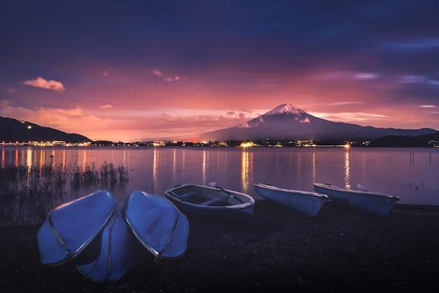 Monte fuji sobre el lago kawaguchiko con barcos al atardecer en fujikawaguchiko, japón.