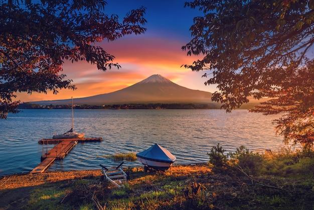 Monte fuji sobre el lago kawaguchiko con follaje otoñal y barco al amanecer en fujikawaguchiko, japón.