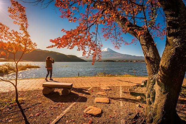 Monte fuji sobre el lago kawaguchiko con follaje otoñal y mujer viajera al amanecer en fujikawaguchiko, japón.