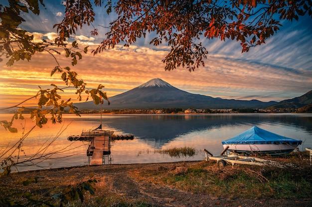 Monte fuji sobre el lago kawaguchiko con follaje de otoño y barco al amanecer en fujikawaguchiko, japón.
