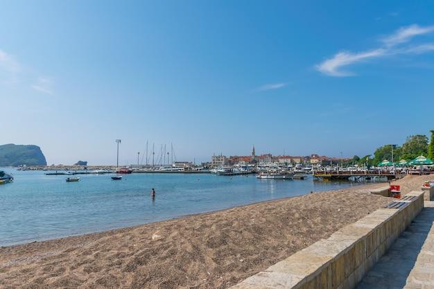 Montenegro audaces turistas se bañan en el agua fresca en la playa cerca de yacht marina