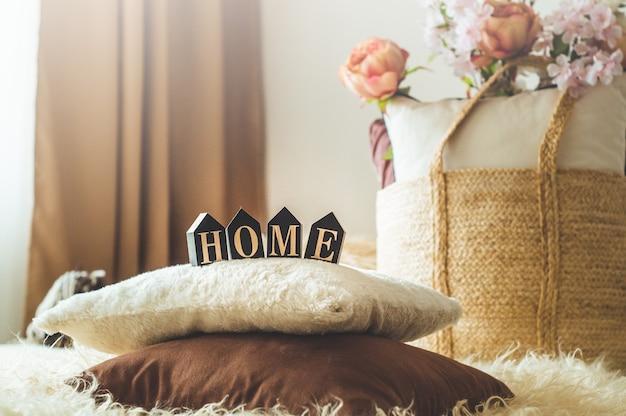 Un montón de acogedoras almohadas decorativas y la inscripción hogar. en el interior de la casa en la cama con una canasta de mimbre y flores. primavera en el interior de la casa. concepto de casa