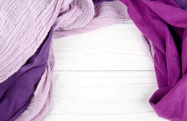 Montón de acogedoras bufandas brillantes formando un marco sobre un fondo blanco de madera