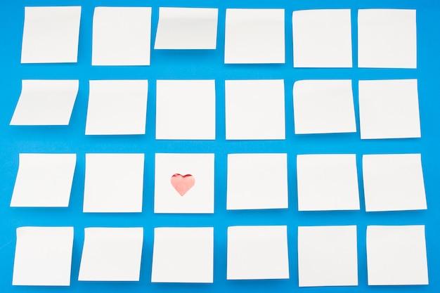 Un montón de adhesivos post-it en blanco con corazones en la pared azul. vista desde arriba