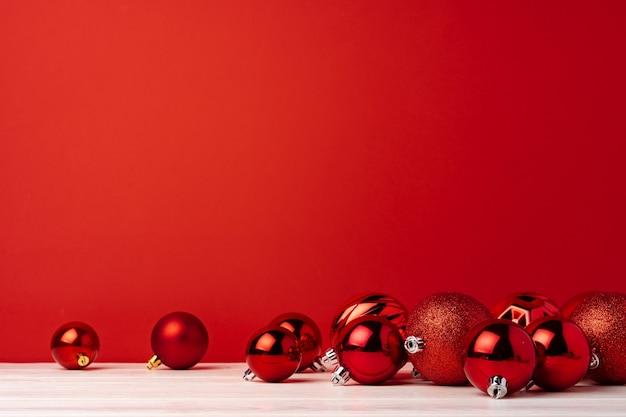 Montón de adornos navideños rojos sobre fondo rojo.