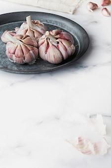 Un montón de ajo morado en un plato rústico sobre un fondo de mármol.
