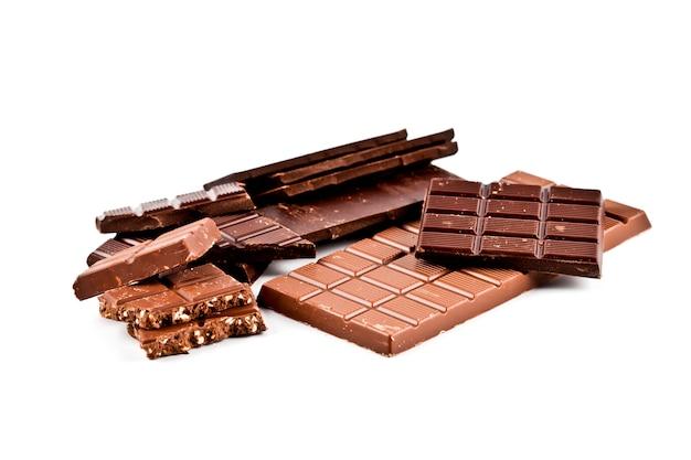 Montón de barras de chocolate con leche y avellanas rotas con avellanas.