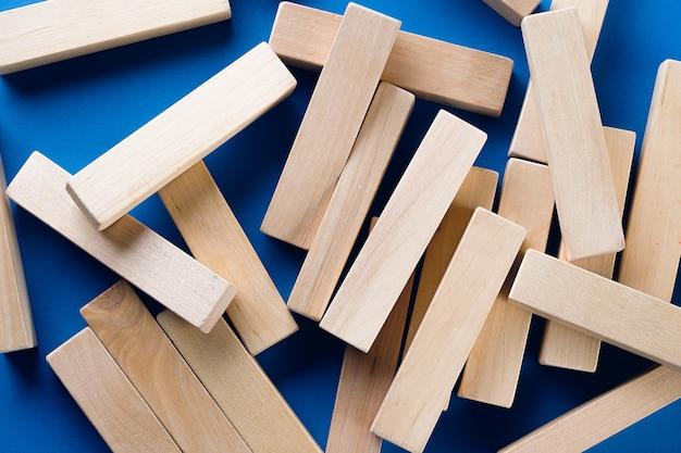 Un montón de bloques de madera dispersos sobre un fondo azul. juego de construcción. destruye la torre. copiar espacio para texto.