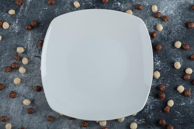 Montón de bolas de cereal esparcidas por un plato blanco.