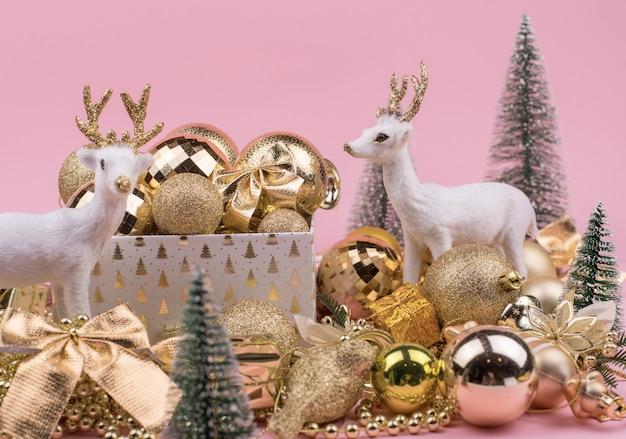 Un montón de bolas navideñas doradas con ciervos en rosa