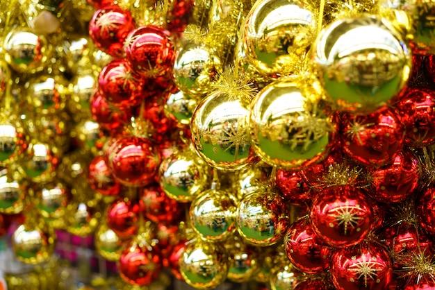 Un montón de bolas rojas y amarillas de cristal de navidad están colgadas en la tienda. decoración festiva de año nuevo