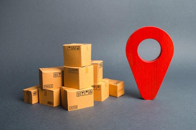 Un montón de cajas de cartón y un pin de posición rojo. localización de paquetes y mercancías.