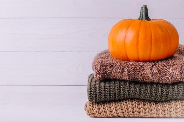 Montón de cálidos suéteres de punto con calabaza