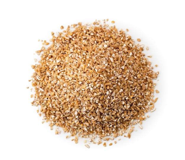Montón de cereales de trigo secos sobre un fondo blanco.