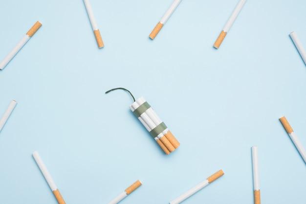 Montón de cigarrillos atados y mecha rodeado de cigarrillos sobre fondo azul
