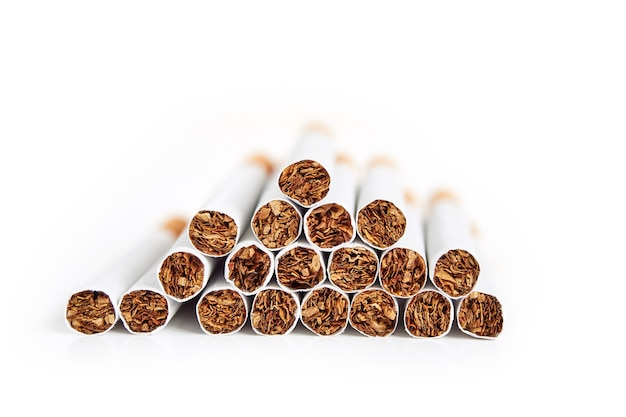 Montón de cigarrillos con filtro sobre superficie blanca aislada