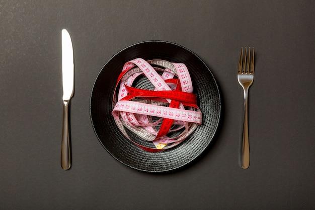 Montón de cinta métrica colorida en lugar de espagueti en plato redondo sobre fondo negro
