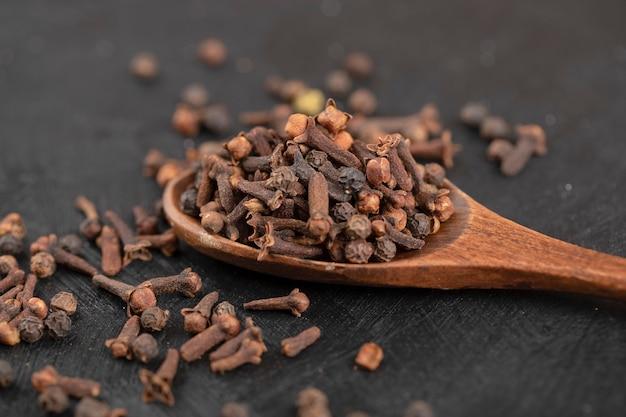 Montón de clavos de olor naturales secos con cuchara de madera sobre superficie negra.
