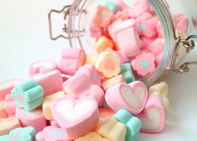 Montón de color pastel en forma de corazón y caramelos de malvavisco en forma de flor esparcidos de un frasco de vidrio