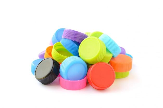 Montón de coloridas tapas de botellas de plástico en blanco