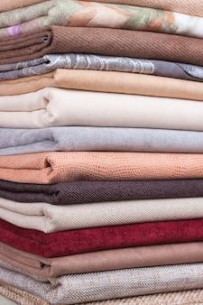 Montón de coloridos textiles plegados. montón de tela de tela