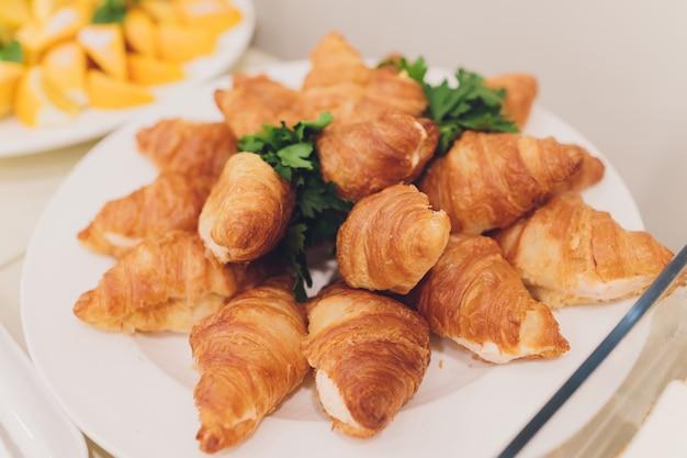 Un montón de cruasanes recién hechos en un plato blanco en el buffet en el restaurante.