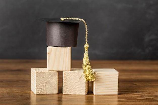 Montón de cubos de madera con gorro de graduación