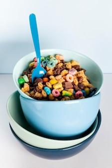 Montón de cuencos azules sucios llenos de aros de frutas de cereales