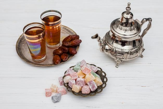 Montón de dátiles secos cerca de tazas de té, delicias turcas y tetera.