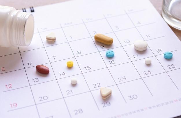 Montón de diferentes pastillas en un fondo de calendario. concepto de salud