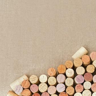 Montón de diferentes tapones de madera de vino tinto y blanco en tela de algodón natural