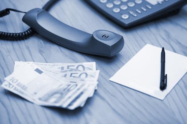 Montón de dinero en la mesa de oficina y teléfono