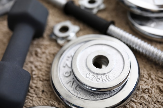 Montón de discos de mancuernas de cromo brillante acostado alrededor de agarre en casa alfombra como ejercicios deportivos domésticos