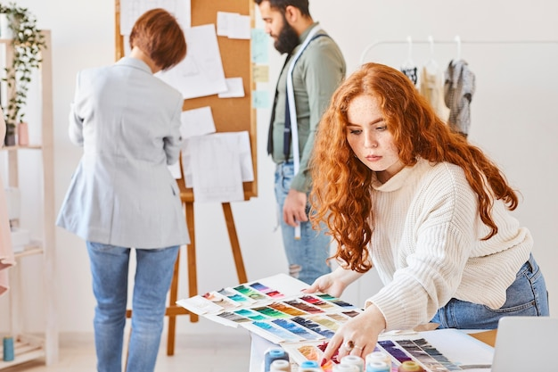 Montón de diseñador de moda trabajando en atelier con paleta de colores