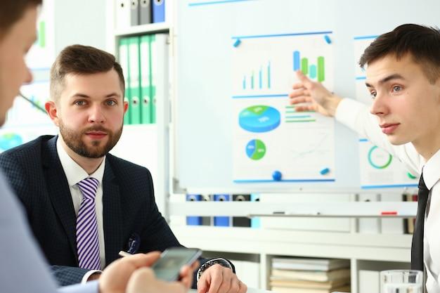 Montón de empresarios sentados en la oficina para resolver problemas actuales