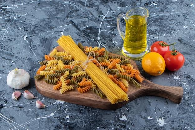 Montón de espaguetis crudos en cuerda con pastas y verduras multicolores.