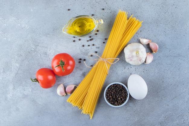 Montón de espaguetis crudos en cuerda con tomates rojos frescos y ajo.