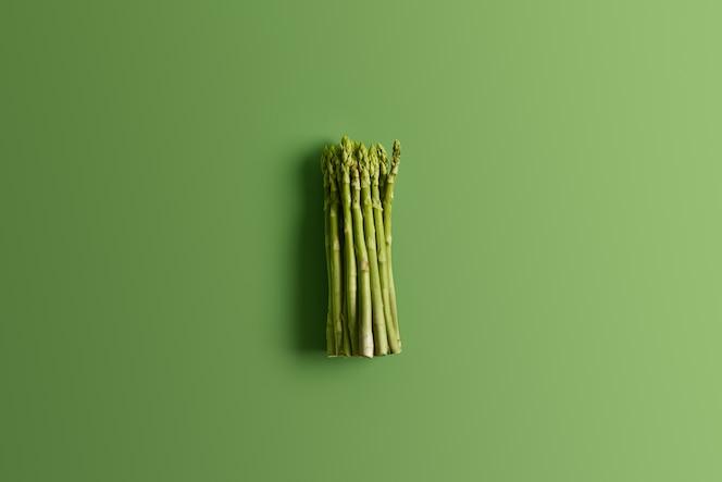 montón de espárragos frescos sobre fondo verde vivo. ingrediente para preparar una deliciosa ensalada vegetariana. concepto de comida. verduras frescas de primavera. brotes comestibles de espárragos ricos en vitaminas, ácido fólico