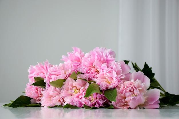 Montón de flores frescas frescas cortadas peonía rosa en flor en mesa blanca