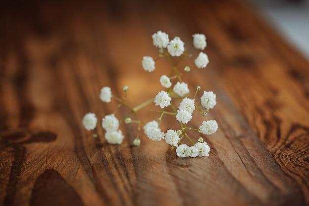Montón de fowers blancos (gypsophila) sobre un fondo de madera, enfoque selectivo