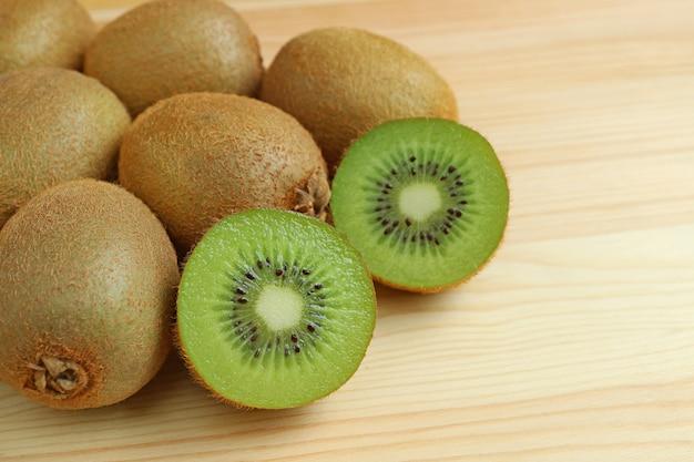Montón de frutas enteras y rodajas de kiwi aislados en mesa de madera