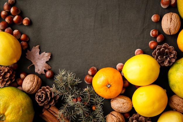 Montón de frutas frescas, conos y nueces sobre la tela verde oscuro. fondo de acción de gracias con copyspace