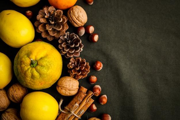 Montón de frutas frescas, conos y nueces sobre la tela verde oscuro