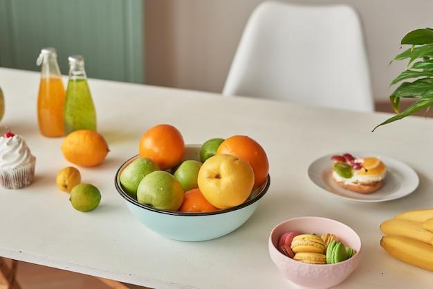 Montón de frutas maduras en la mesa con dulces macarons y jugos