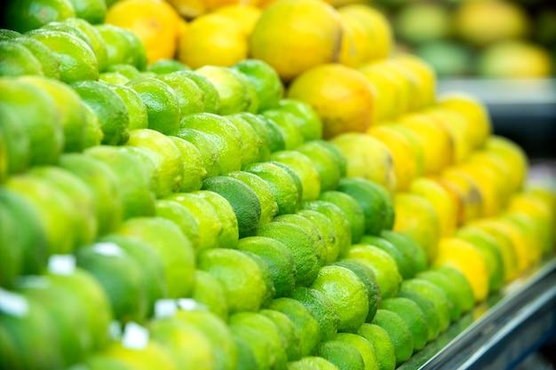 Montón de una gran cantidad de limones frescos verdes para la venta en el supermercado.