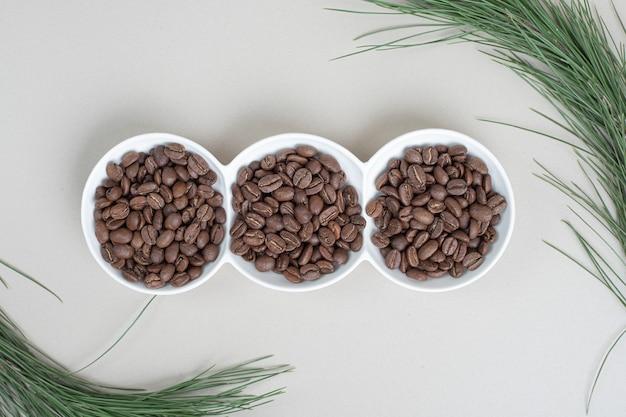 Montón de granos de café en la placa blanca.