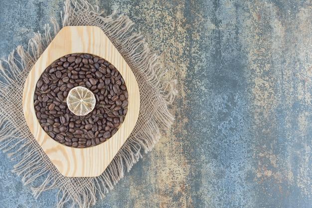 Montón de granos de café y una rodaja de limón en un plato de madera.