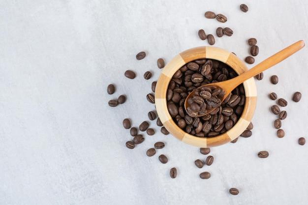 Montón de granos de café en un tazón de madera con cuchara