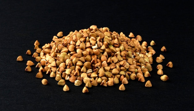 Montón de granos de trigo sarraceno verde aislado sobre fondo negro, primer plano