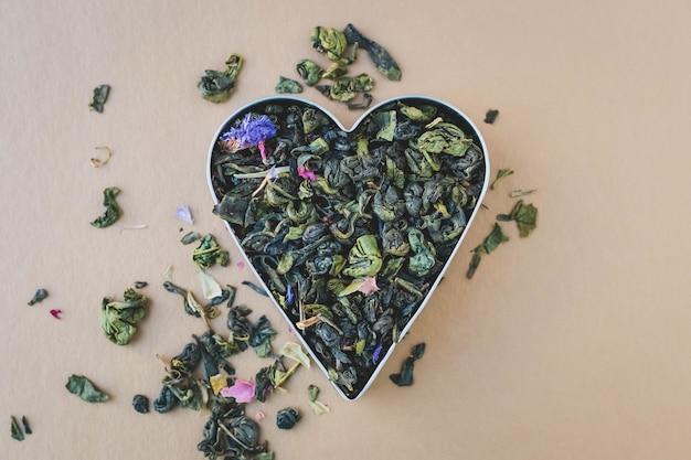 Montón de hojas de té verde. en forma de corazon. mezcla de té de hierbas.